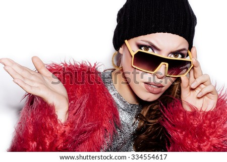 Fashion female model in sunglasses wearing silver dress pink fur coat black beanie hat .  White background, not isolated - stock photo