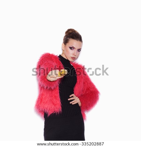 Fashion female model wearing black dress and pink fur coat making fun with banana. Cute woman having fun over white background not isolated - stock photo