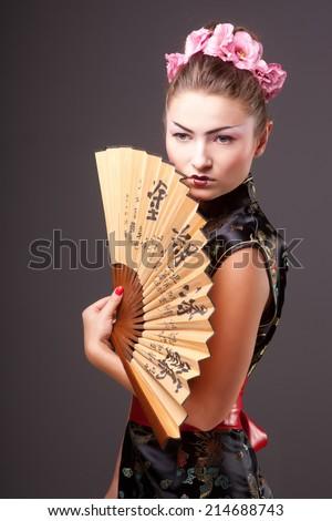 Fashion geisha  in studio with fan - stock photo