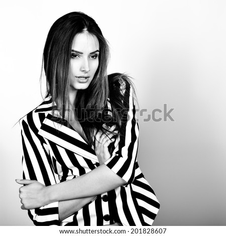 Fashion girl, black and white. Young sexy brunette woman posing at studio in striped jacket, white shorts. - stock photo