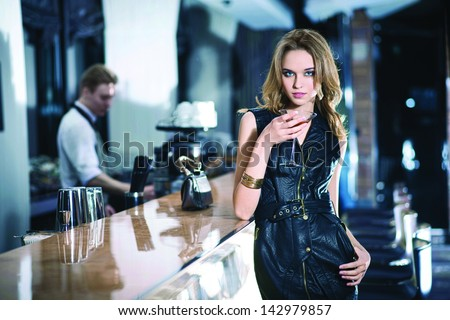 Fashion girl drinking a cocktail - stock photo