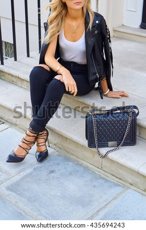 Fashion girl in black jeans sitting on whit stairs outside, white top and black leather jacket  - stock photo
