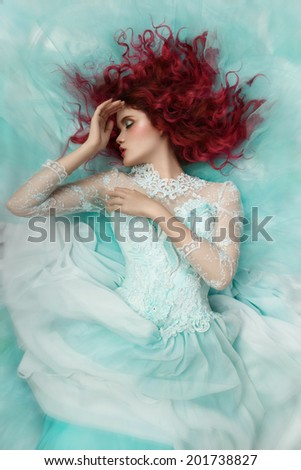 fashion girl lying in a turquoise dress - stock photo