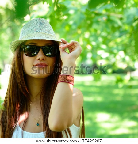 fashion girl outdoor portrait, young woman walking in summer park  in sunglasses and fedora with long brown hair - stock photo