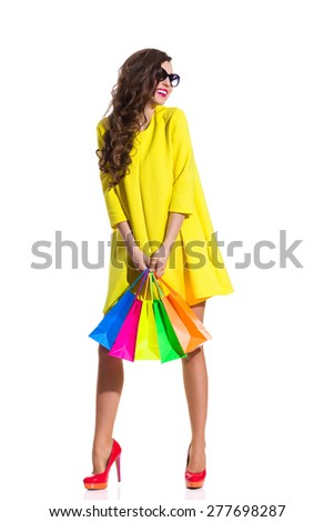 Fashion Girl Shopping. Smiling elegance young woman in red high heels and yellow mini dress standing and holding colorful shopping bags. Full length studio shot isolated on white. - stock photo