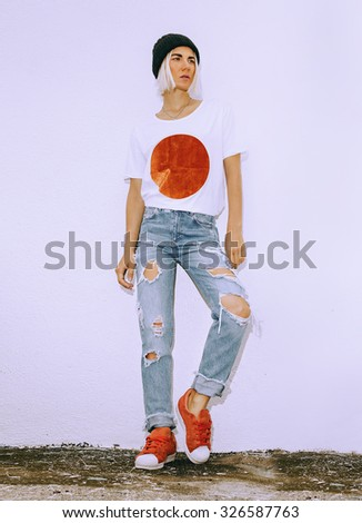 Fashion Girl style. Torn vintage jeans and fashionable T-shirt - stock photo