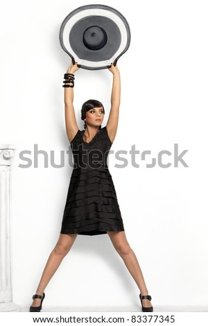 Fashion girl with a big hat in the studio - stock photo