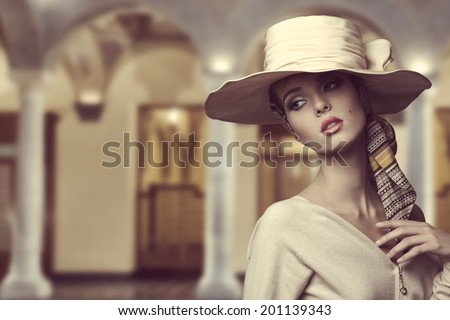 fashion girl with big elegant hat and foulard on the head posing with beige dress and sensual expression  - stock photo