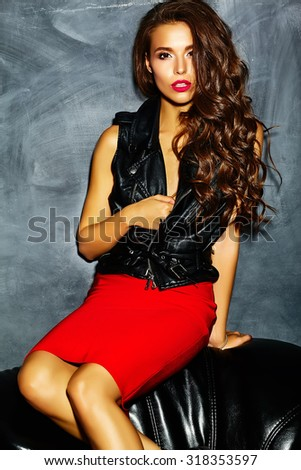 fashion glamor stylish beautiful  funny crazy young woman model with red lips in summer bright colorful hipster  red clothes sitting on black sofa near gray wall - stock photo