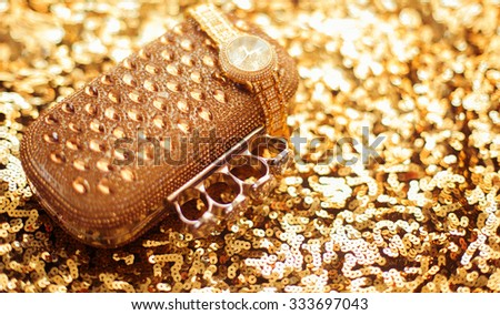 Fashion golden womens accessories. Rich wristwatch and purse, on golden sequins sparkling sequined textile. Luxury set closeup. - stock photo