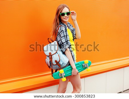 Fashion happy smiling hipster cool girl in sunglasses with skateboard and backpack having fun against the colorful orange wall - stock photo