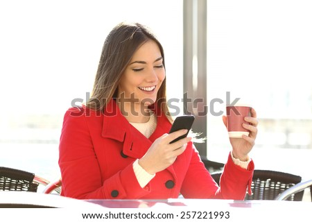 Fashion happy woman using a smartphone in a coffee shop and holding a cup ready to drink - stock photo
