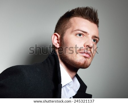Fashion Head Shot of a young man in coat. He is now a professional model  - stock photo