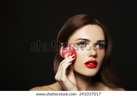 Fashion, health, beauty and spa concept - beautiful woman with rose leaf sponge and red lips, in black background - stock photo