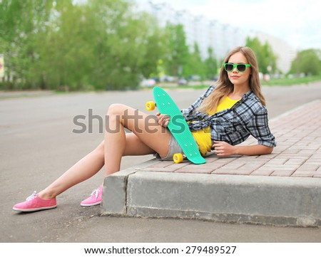 Fashion hipster girl in sunglasses with skateboard posing outdoors - stock photo
