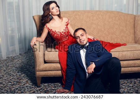 fashion interior photo of beautiful tender couple in elegant clothes posing in bedroom - stock photo