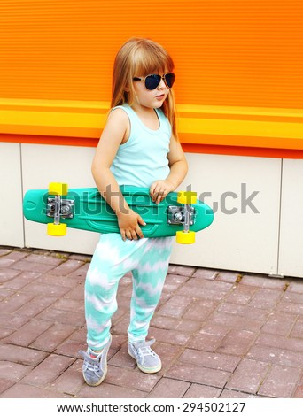 Fashion kid concept - stylish little girl child wearing a t-shirt and sunglasses with skateboard in the city summer  - stock photo