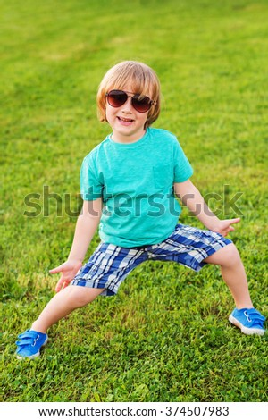 Fashion kid, cute little boy wearing turquoise shirt, blue shorts and shoes - stock photo