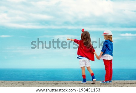 Fashion kids stands on stone breakwater and points to the sea. Vacation, friendship, fashionable concept. - stock photo