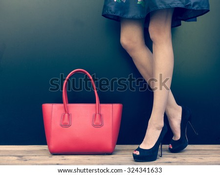 Fashion leggy girl in a beautiful high-heeled shoes in short denim dress summer posing near the dark wall. Close-up. Warm color - stock photo