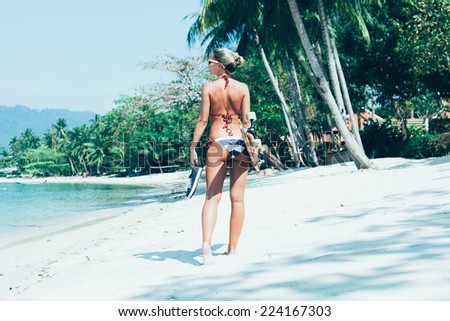Fashion lifestyle outdoors. Sporty girl with longboard in hand walking on white sand on tropical beach - stock photo