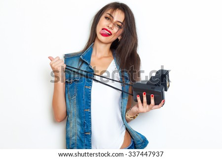Fashion lifestyle portrait of happy pretty woman laughing and shows tongue,stylish vintage retro camera,bright fresh colors.toned body,polaroid photo camera,denim outfit,80e style,white background - stock photo