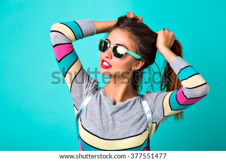Fashion lifestyle portrait of joyful funny woman, sexy full lips, mirrored sunglasses, holding her hairs like two ponytails, spring colors, mint background. cute emotions, trendy woman. - stock photo