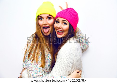 Fashion lifestyle portrait of pretty blonde and brunette funny girls,best friends and sisters, neon hipster hats, natural make up, trendy pastel sweaters. Showing long tongue , grimaces, crazy. - stock photo