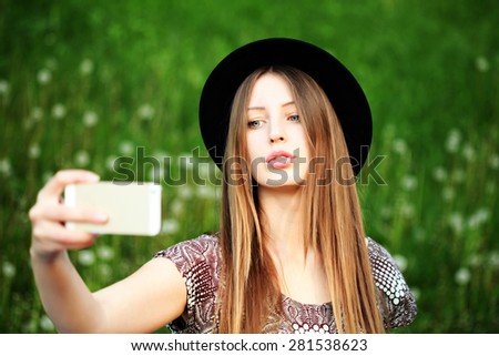 Fashion lifestyle portrait of young lovely woman wearing a trendy hat, a bohemian dress and making selfie on flowers meadow. Young fashionable hippie girl outdoor - stock photo
