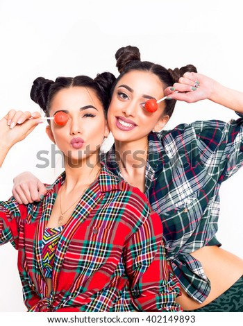 fashion lifestyle portrait two teen girls,attractive fancy friends in colorful hipster fashionable outfit .Women holding pink lolly pop and having fun together at white background.Isolated  - stock photo