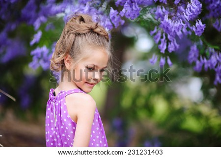 Fashion little girl model in blooming jacaranda garden. Kid hair style. - stock photo