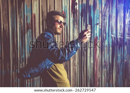 fashion male model taking photos with a phone - stock photo