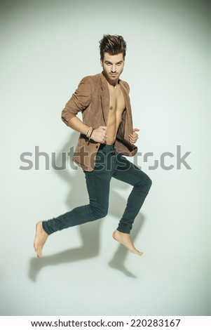 Fashion man jumping while looking at the camera, pulling his jacket on grey background - stock photo