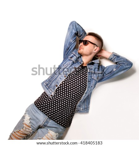 fashion man lies on a white background wearing sunglasses and smiling. The concept of the office holiday - stock photo