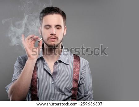 Fashion man smoking a cigarette on gray background - stock photo