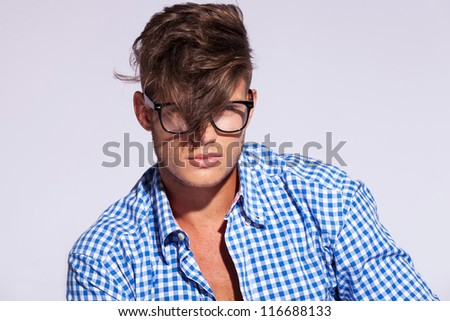 fashion man wearing glasses and his hair over his face on gray background - stock photo