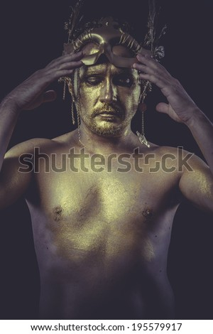 Fashion, Man with body painted gold feather mask and steel sword - stock photo