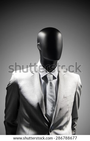Fashion mannequin in elegant suit over dark grey background. Black White photo - stock photo