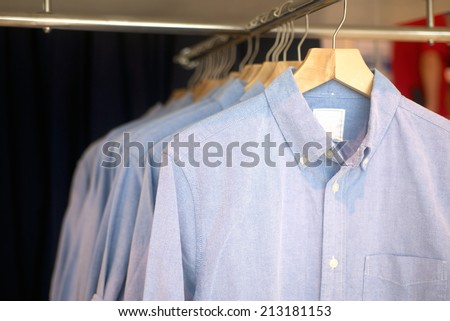 fashion men's shirts hanging in trendy boutique - stock photo