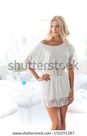 Fashion model. Attractive young blond hair woman in white dress holding her hand on hip and looking away - stock photo