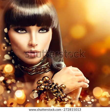 Fashion model brunette girl with golden accessories over gold shiny background. Golden Jewellery. Gold Jewelry. Beauty Egyptian Style Woman with Gold Accessories. Golden bracelet and Necklace - stock photo