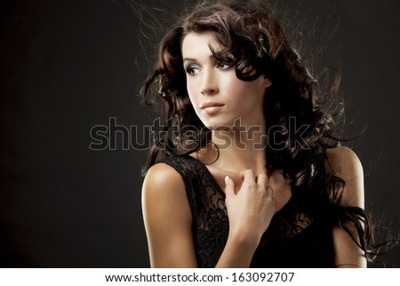 fashion model brunette wearing black outfit on black background - stock photo