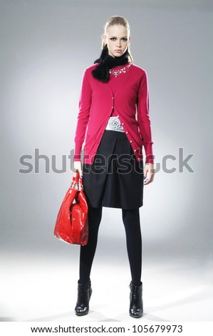 fashion model holding red hand bag posing in light background - stock photo