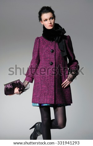 fashion model in autumn/winter clothes with scarf holding handbag posing - stock photo