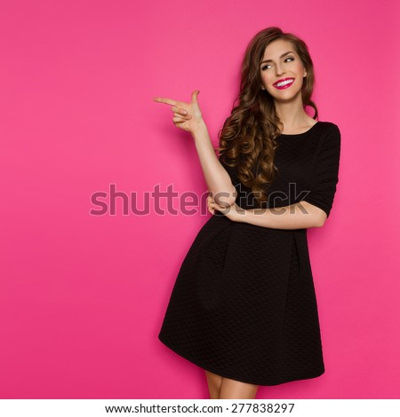 Fashion Model In Black Dress Pointing. Smiling elegance woman in black mini dress standing, pointing and looking away. Three quarter length studio shot on pink background. - stock photo