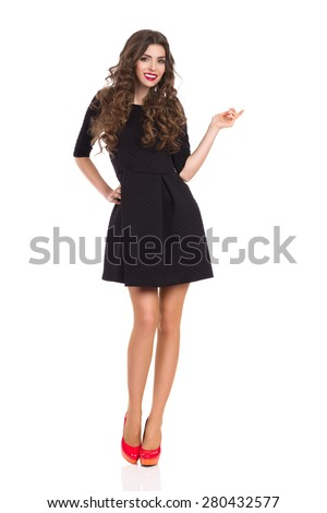 Fashion Model in Black Mini Dress Pointing. Full length on white background. - stock photo