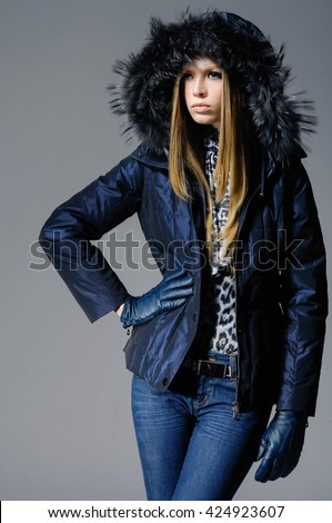 fashion model in coat clothes posing-gray background  - stock photo