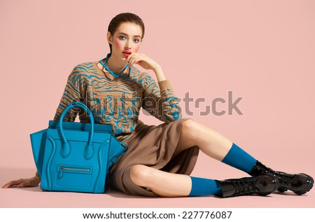 Fashion model in design clothes and blue bag posed on light color background - stock photo