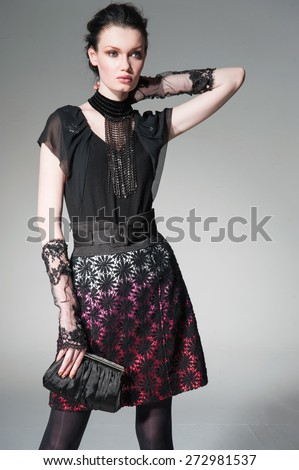 fashion model in fashion dress holding purse in the studio - stock photo