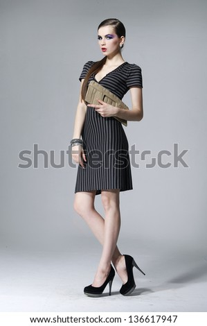 fashion model in fashion dress holding purse walking in studio posing - stock photo